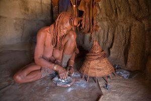 Eine Himba Frau parfümiert ihre Kleidung